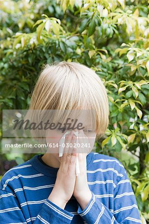 Boy blowing his nose Stock Photo - Premium Royalty-Free, Image code: 614-03020241