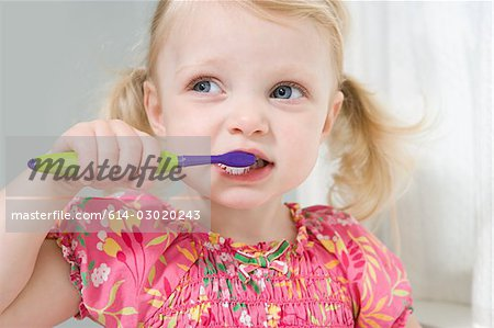 Little girl brushing her teeth Stock Photo - Premium Royalty-Free, Image code: 614-03020243