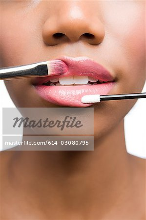 Woman having lipgloss applied Stock Photo - Premium Royalty-Free, Image code: 614-03080795