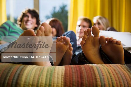 Friends on bed with bare feet Stock Photo - Premium Royalty-Free, Image code: 614-03241360
