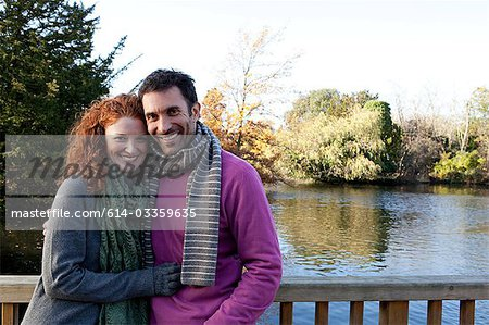 Portrait of a happy couple on a river bridge Stock Photo - Premium Royalty-Free, Image code: 614-03359635