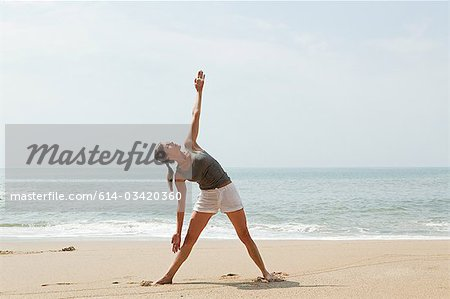 Woman practicing yoga on a beach Stock Photo - Premium Royalty-Free, Image code: 614-03420360
