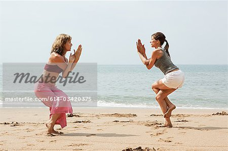 Two women practicing yoga on a beach Stock Photo - Premium Royalty-Free, Image code: 614-03420375