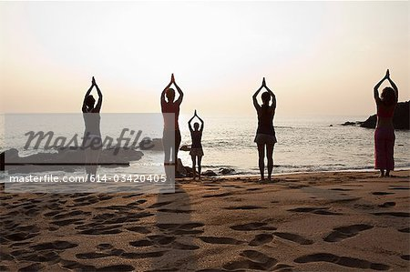 Women practicing yoga on beach at sunset Stock Photo - Premium Royalty-Free, Image code: 614-03420405