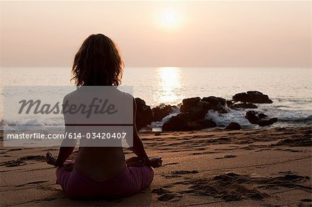 Woman practicing yoga on beach at sunset Stock Photo - Premium Royalty-Free, Image code: 614-03420407