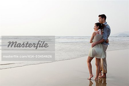Couple looking out to the ocean Stock Photo - Premium Royalty-Free, Image code: 614-03454626