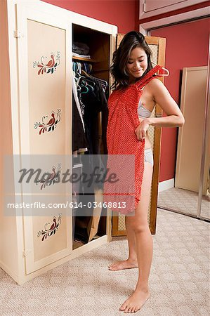 Young woman choosing clothes Stock Photo - Premium Royalty-Free, Image code: 614-03468813