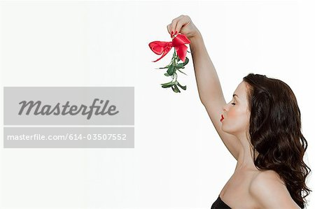 Young woman blowing a kiss Stock Photo - Premium Royalty-Free, Image code: 614-03507552