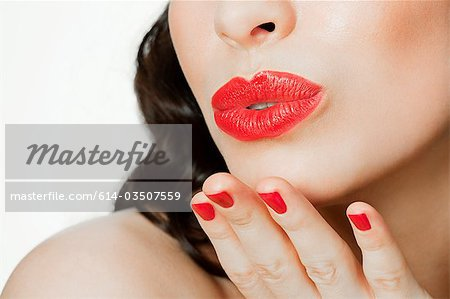 Young woman blowing a kiss Stock Photo - Premium Royalty-Free, Image code: 614-03507559