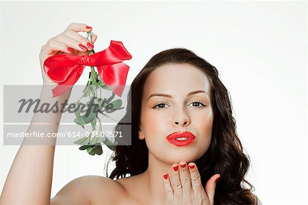 Young woman blowing a kiss holding mistletoe Stock Photo - Premium Royalty-Free, Image code: 614-03507571