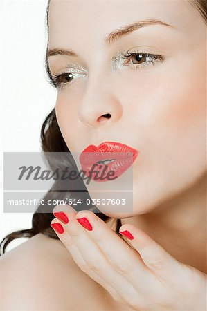 Young woman blowing a kiss Stock Photo - Premium Royalty-Free, Image code: 614-03507603