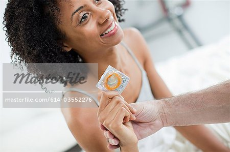 Woman with condom and hand of partner Stock Photo - Premium Royalty-Free, Image code: 614-03552276