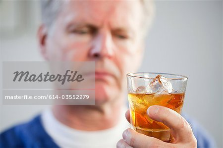 Man with glass of whisky Stock Photo - Premium Royalty-Free, Image code: 614-03552279