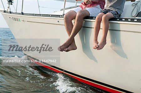 Father and son sitting on yacht, legs dangling Stock Photo - Premium Royalty-Free, Image code: 614-03647942