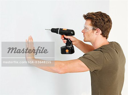 Young man using electric drill Stock Photo - Premium Royalty-Free, Image code: 614-03648155