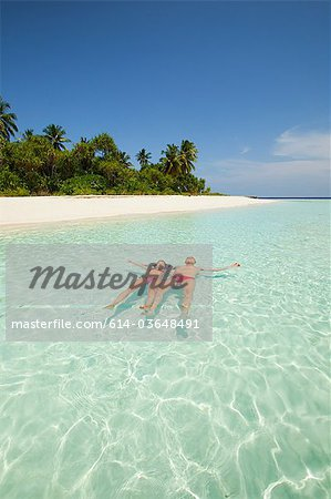 Couple floating in the sea, Baughagello Island, South Huvadhu Atoll, Maldives Stock Photo - Premium Royalty-Free, Image code: 614-03648491