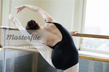 Ballerina stretching at barre Stock Photo - Premium Royalty-Free, Image code: 614-03684432