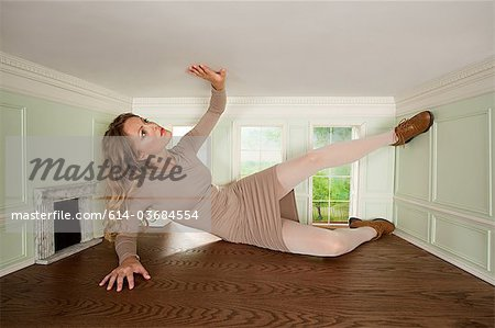 Giant young woman trapped in small room Stock Photo - Premium Royalty-Free, Image code: 614-03684554