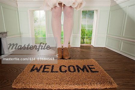 Legs of a woman and welcome mat in small room Stock Photo - Premium Royalty-Free, Image code: 614-03684563