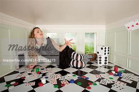 Young woman in small room throwing playing card Stock Photo - Premium Royalty-Free, Image code: 614-03684573