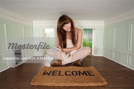 Young woman sitting in small room with welcome mat Stock Photo - Premium Royalty-Free, Image code: 614-03684575