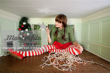 Young woman in small room with christmas decorations Stock Photo - Premium Royalty-Free, Image code: 614-03684586