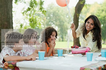 Children at birthday party with birthday cake Stock Photo - Premium Royalty-Free, Image code: 614-03697231