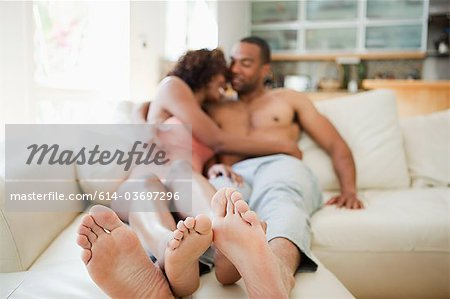 Couple on sofa, focus on feet in foreground Stock Photo - Premium Royalty-Free, Image code: 614-03697296