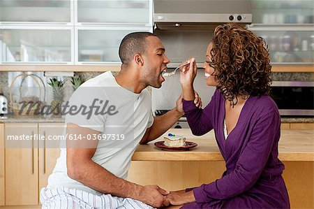 Woman feeding cake to boyfriend Stock Photo - Premium Royalty-Free, Image code: 614-03697319