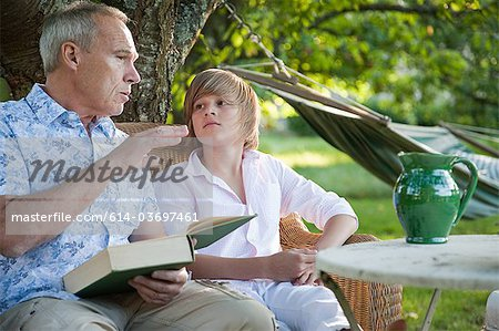 Father and son with book, in conversation Stock Photo - Premium Royalty-Free, Image code: 614-03697461