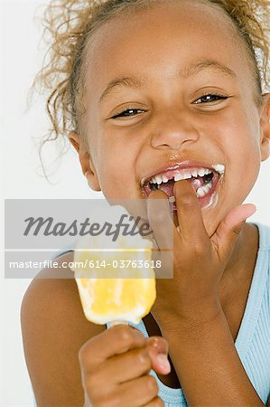 Girl eating ice lolly Stock Photo - Premium Royalty-Free, Image code: 614-03763618