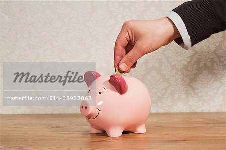 Man inserting pound coin into piggy bank Stock Photo - Premium Royalty-Free, Image code: 614-03903063