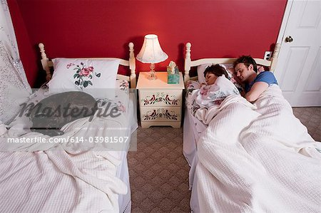 Young couple sharing single bed, dog asleep on other bed Stock Photo - Premium Royalty-Free, Image code: 614-03981507