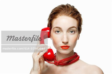 Woman with red telephone cord wrapped around neck Stock Photo - Premium Royalty-Free, Image code: 614-03982061