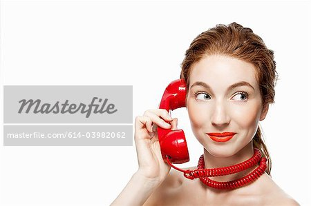 Woman with red telephone cord wrapped around neck Stock Photo - Premium Royalty-Free, Image code: 614-03982062