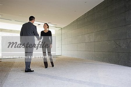Businesspeople shaking hands in empty office Stock Photo - Premium Royalty-Free, Image code: 614-05399601