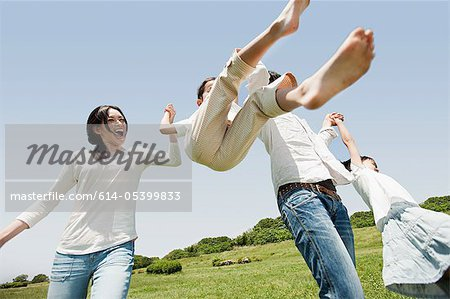 Parents lifting son mid air Stock Photo - Premium Royalty-Free, Image code: 614-05399833