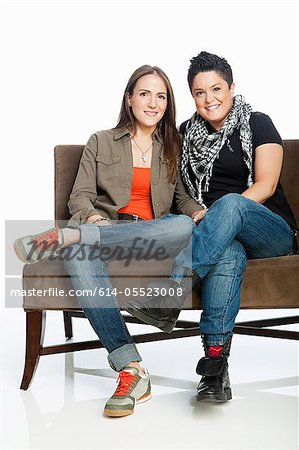 Lesbian couple on sofa against white background Stock Photo - Premium Royalty-Free, Image code: 614-05523008