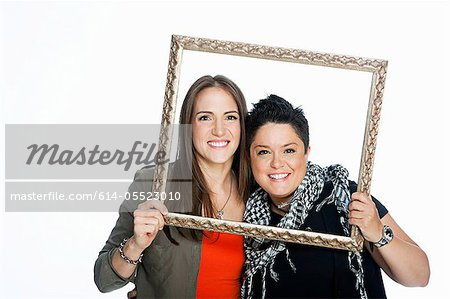 Lesbian couple holding picture frame against white background Stock Photo - Premium Royalty-Free, Image code: 614-05523010