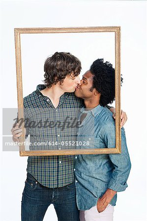 Gay couple kissing with picture frame against white background Stock Photo - Premium Royalty-Free, Image code: 614-05523028