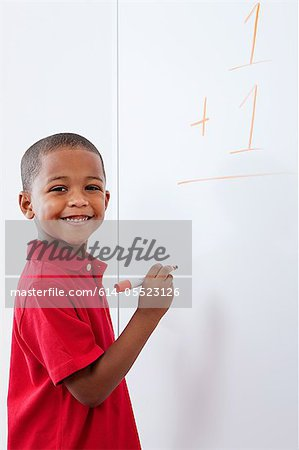 Boy with sum on whiteboard Stock Photo - Premium Royalty-Free, Image code: 614-05523126