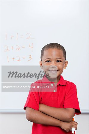 Happy schoolboy in front of mathematics on whiteboard Stock Photo - Premium Royalty-Free, Image code: 614-05523128