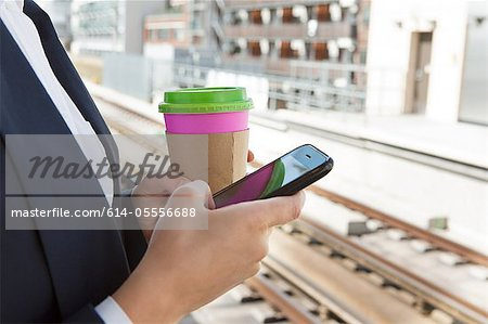 Close up of woman with coffee and smart phone in train station Stock Photo - Premium Royalty-Free, Image code: 614-05556688