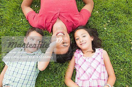 Father lying on grass with son and daughter Stock Photo - Premium Royalty-Free, Image code: 614-05556861