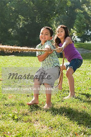 Brother and sister playing tug of war in park Stock Photo - Premium Royalty-Free, Image code: 614-05556867