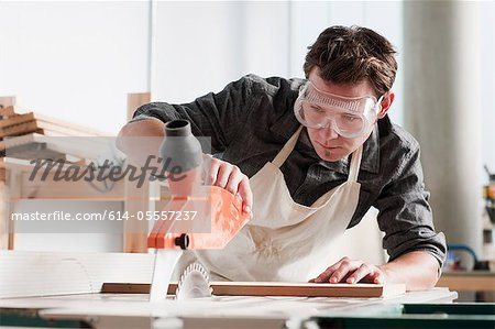 Carpenter using saw in workshop Stock Photo - Premium Royalty-Free, Image code: 614-05557237