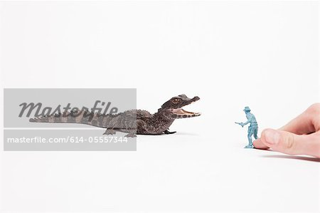 Small reptile attacking toy soldier Stock Photo - Premium Royalty-Free, Image code: 614-05557344