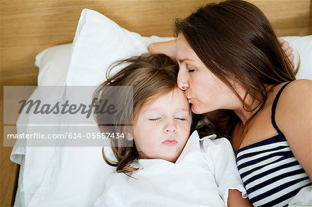Mid adult woman kissing sleeping daughter Stock Photo - Premium Royalty-Free, Image code: 614-05557434