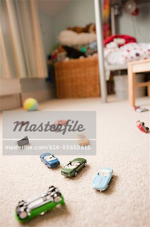 Toy cars scattered across a child's bedroom Stock Photo - Premium Royalty-Free, Image code: 614-05650615