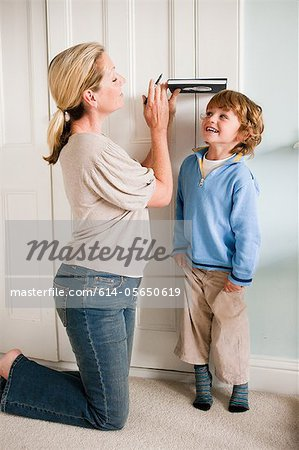 Mother measuring her son against a door with a book Stock Photo - Premium Royalty-Free, Image code: 614-05650619
